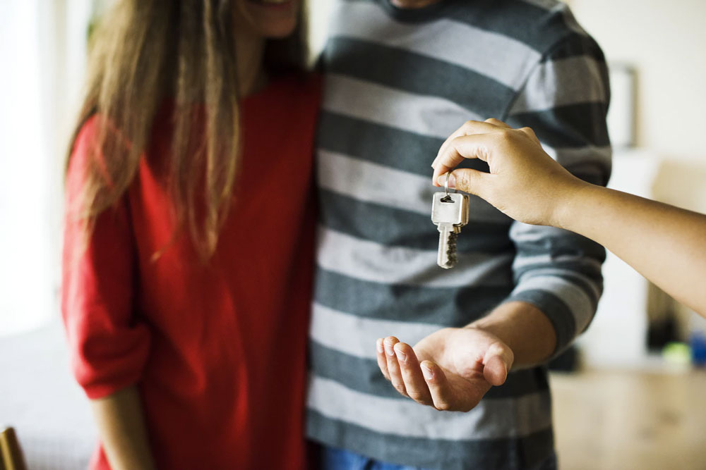 Young couple being given keys to a rental property.